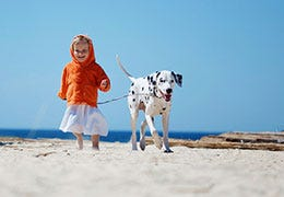 girl walking dog on beach
