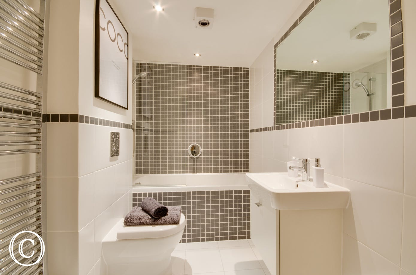 Bright fitted bathroom with shower over bath