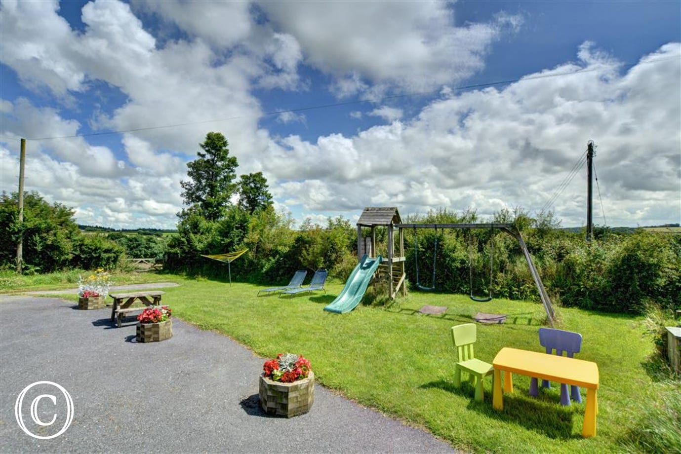 Large communal area with play equipment to the front of the property
