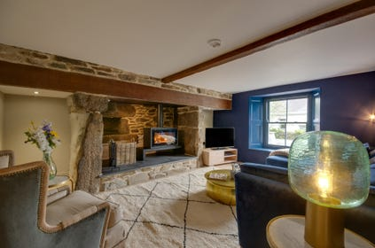 Cosy living room with huge inglenook fireplace with woodburner